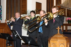 Holy Cross members playing brass insturments in church